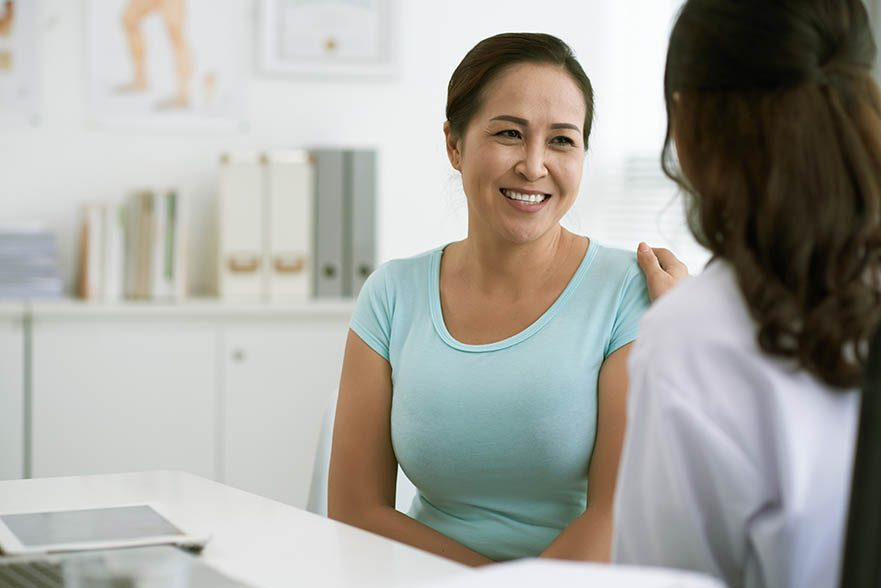 Woman in light green shirt smiling at female doctor